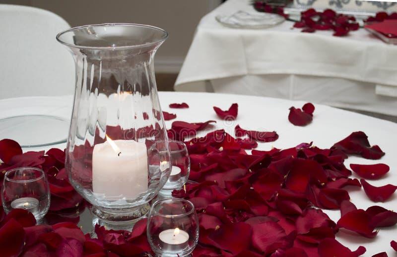 在表上的蜡烛和玫瑰花瓣中心部分 库存图片