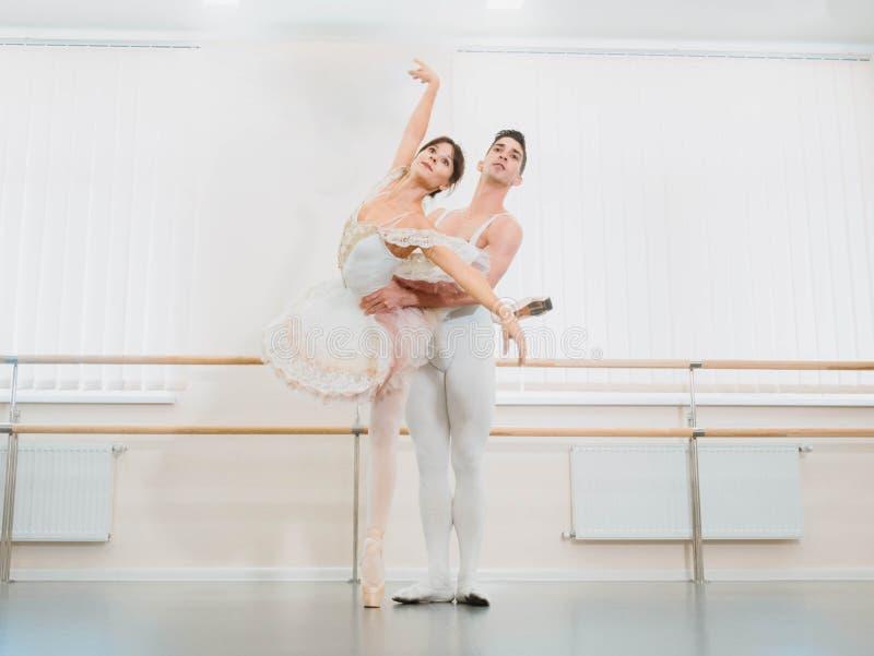 在表现前的训练 人跳舞古典芭蕾,他白色芭蕾舞短裙礼服的转动的俏丽的妇女在健身房或芭蕾 免版税库存照片