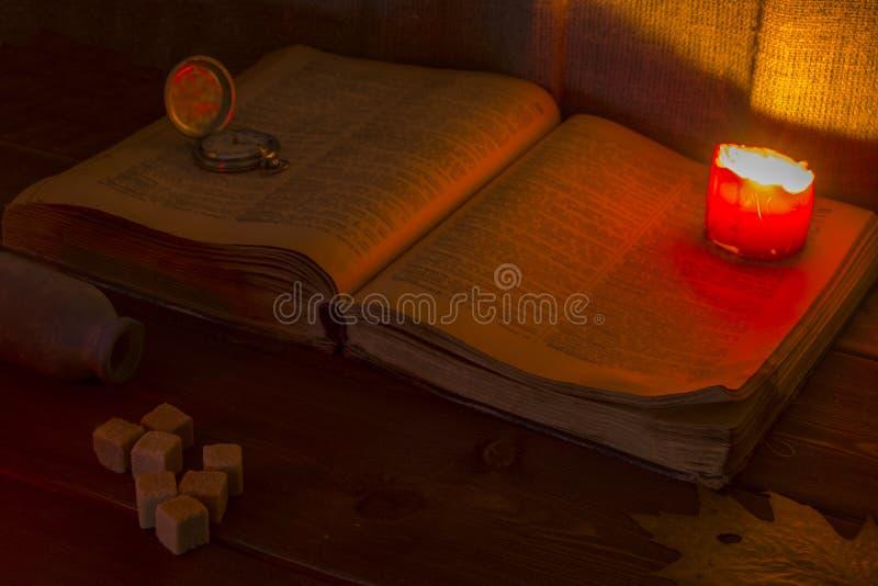 在表的旧书 开放圣经在桌上 葡萄酒怀表 在圣经的一个灼烧的蜡烛照亮它 免版税库存图片