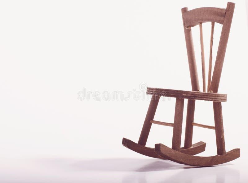 在表达木的地板上的微型椅子偏僻的感觉和失踪某人概念 免版税库存图片