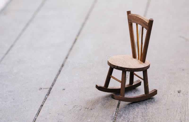 在表达木的地板上的微型椅子偏僻的感觉 免版税库存图片
