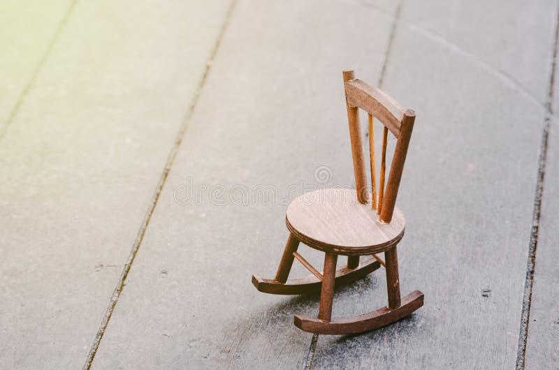 在表达木的地板上的微型椅子偏僻的感觉 免版税库存照片