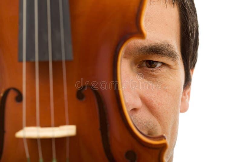 在表面之后隐藏的人小提琴 库存图片
