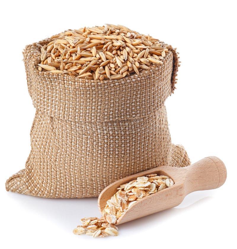 在袋子和燕麦剥落的燕麦五谷在木瓢 免版税库存照片