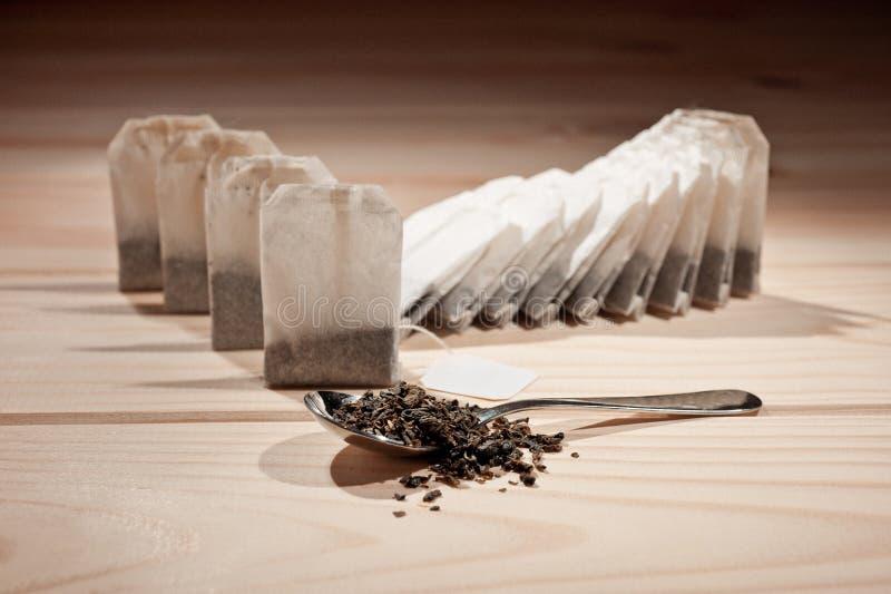在袋子的茶和在一把匙子的宽松茶木表面上 图库摄影