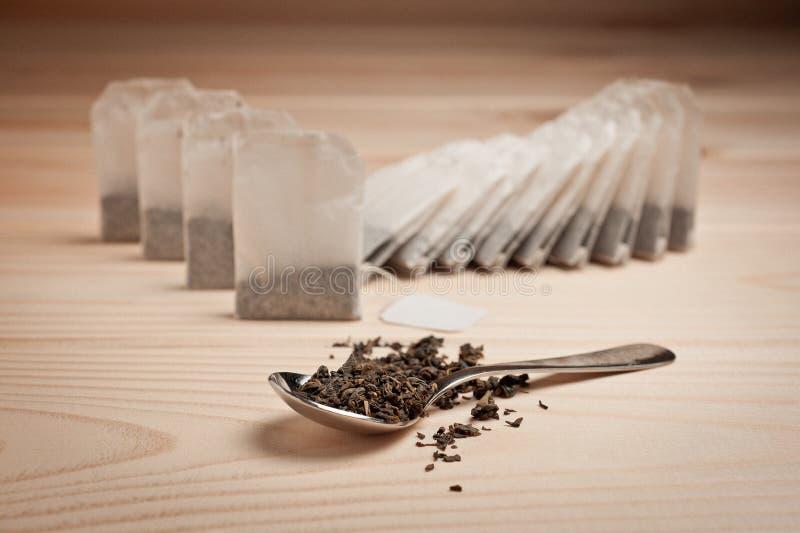 在袋子的茶和在一把匙子的宽松茶木表面上 库存照片