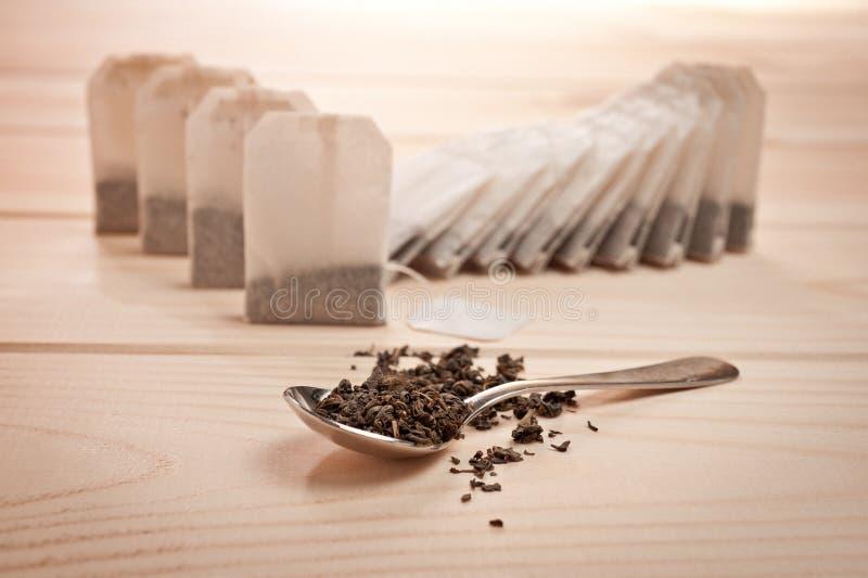 在袋子的茶和在一把匙子的宽松茶木表面上 免版税库存图片