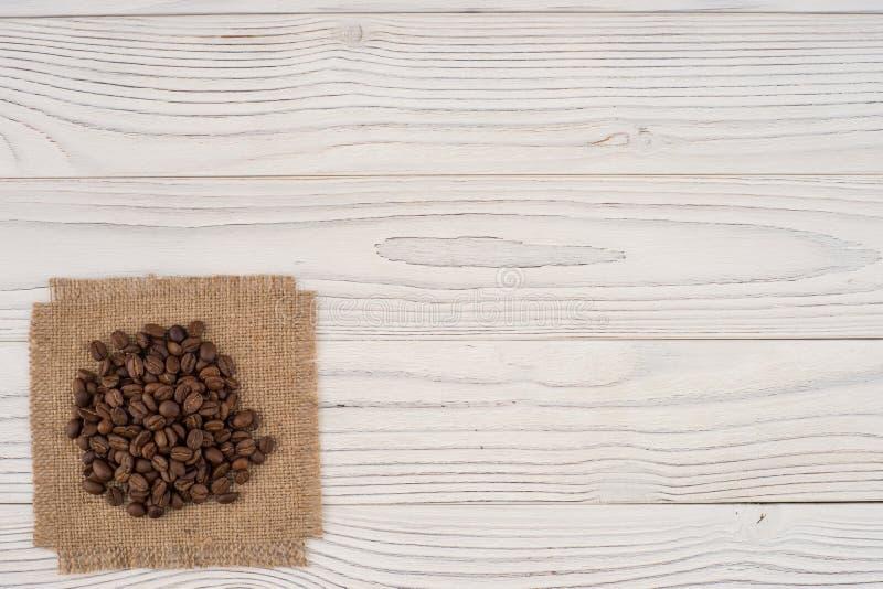 在袋装和一张老白色桌的咖啡豆 库存图片