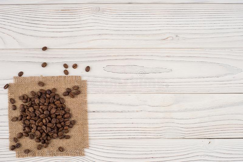 在袋装和一张老白色桌的咖啡豆 库存照片