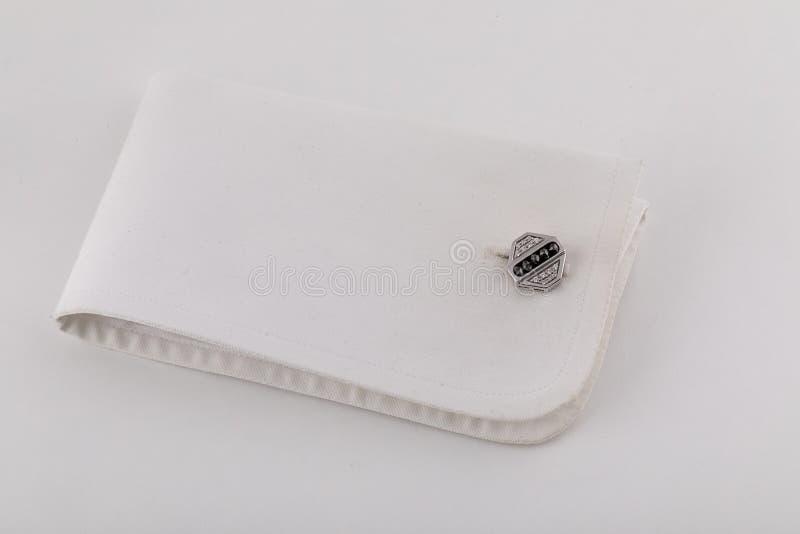 在袖口的银色袖扣以与在白色背景隔绝的石头的一rhomb的形式 免版税库存图片