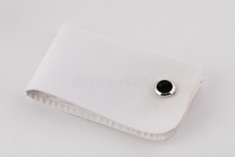 在袖口的银色袖扣以与在白色背景隔绝的黑石头的一个圈子的形式 库存照片