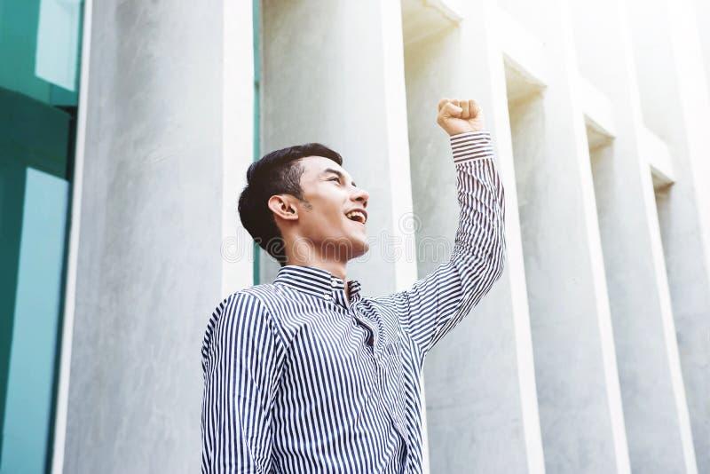 在被举的胳膊的亚洲年轻人和幸福商人在快乐 库存图片