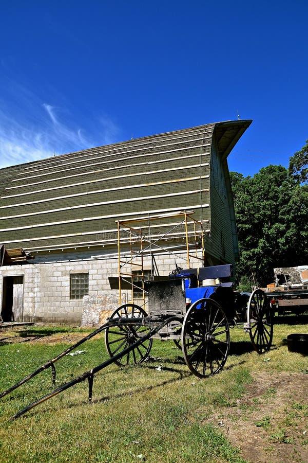 在被修理的老谷仓屋顶前面的门诺派中的严紧派的儿童车 免版税图库摄影