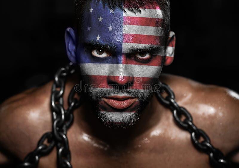 在被囚禁一个年轻的人的面孔的美国国旗 库存照片