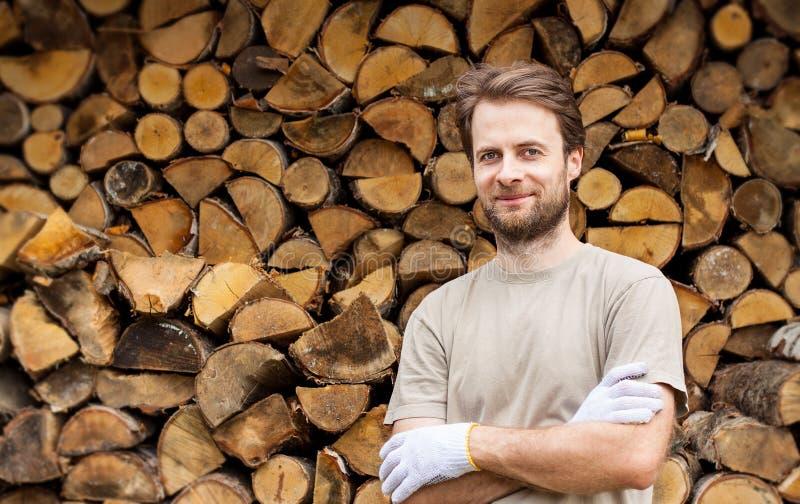 在被堆积的切好的木柴前面的愉快的微笑的人 库存照片