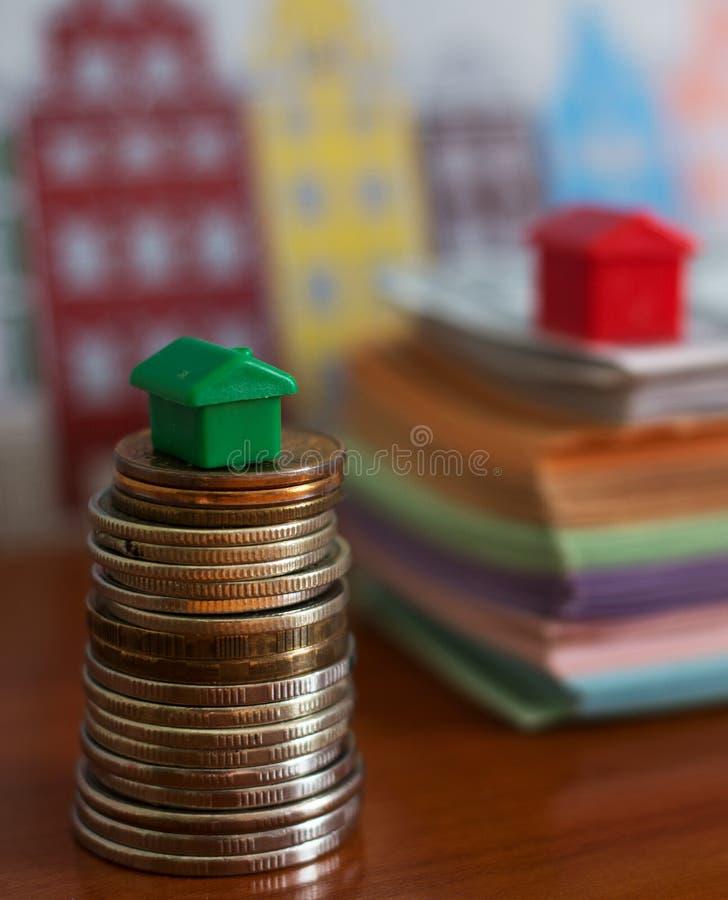 在被堆积的硬币顶部的小塑料房子模型 库存图片