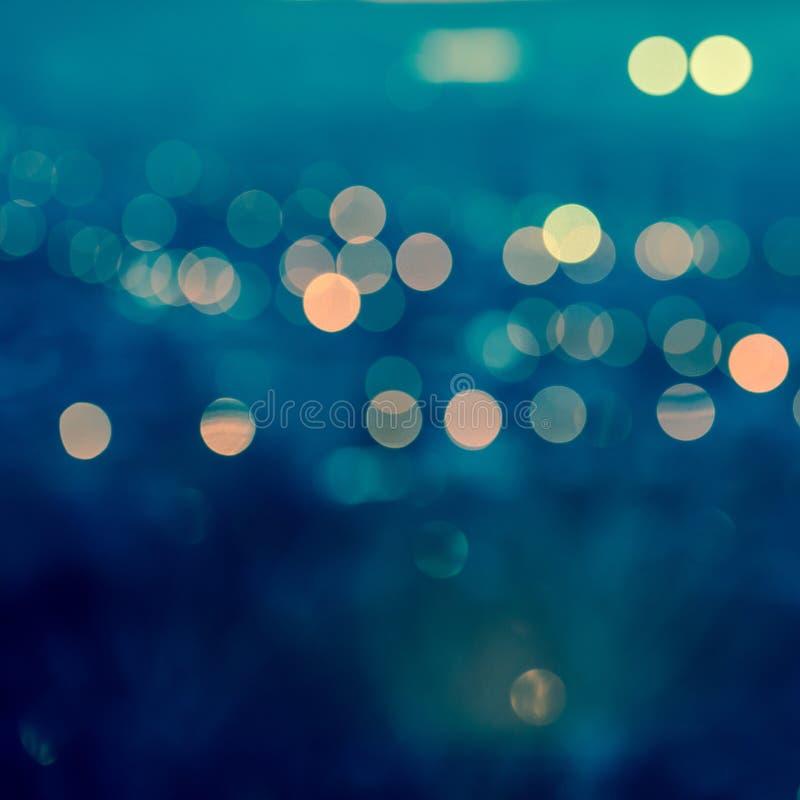 在被定调子的蓝色backg的城市弄脏的光抽象圆bokeh 免版税库存照片