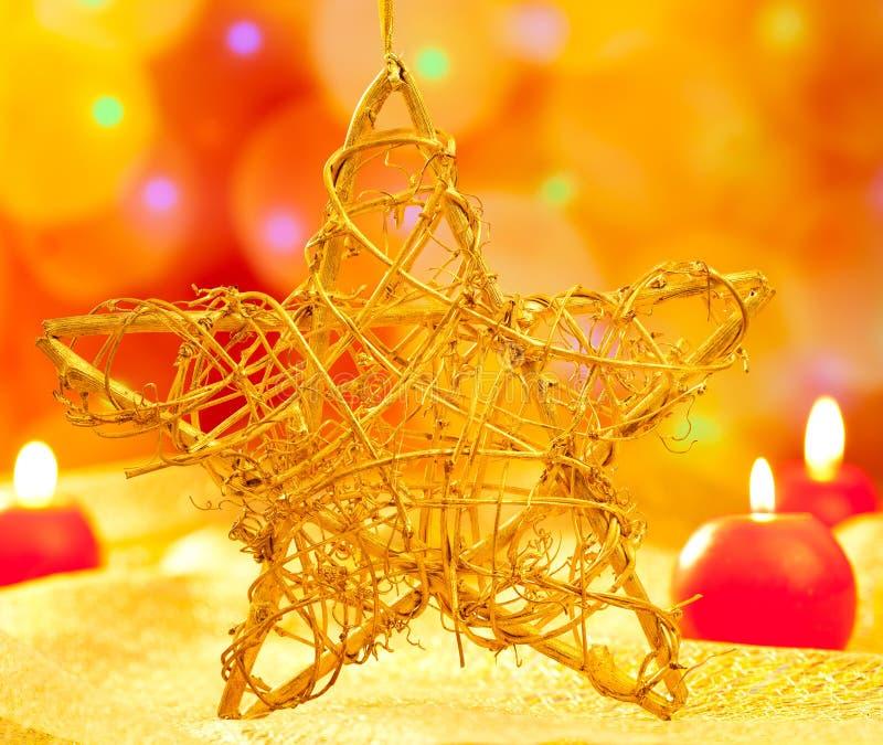 在被弄脏的光的圣诞节金黄星形蜡烛 免版税库存照片