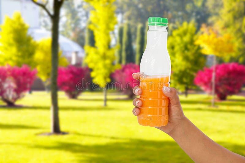 在被弄脏的公园背景,健康生活方式概念的黑女性手举行橙汁过去瓶 免版税库存图片