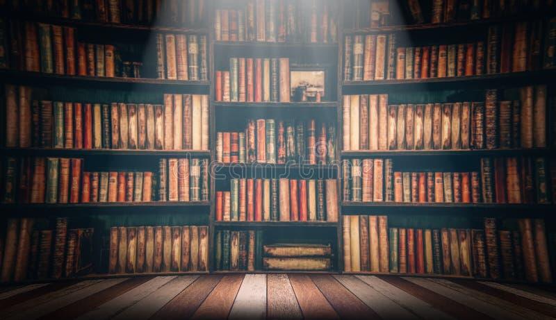 在被弄脏的图象的木桌在书架的许多旧书在图书馆里 库存照片
