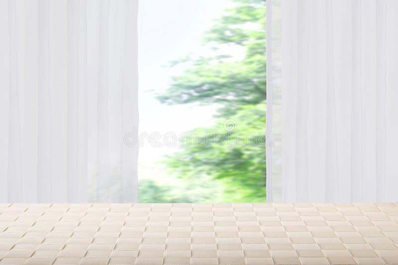 在被弄脏的帷幕窗口自然gr前面的空的明亮的桌 免版税库存图片