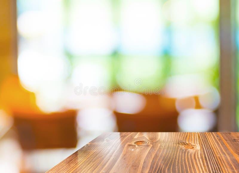 在被弄脏的庭院咖啡馆背景,模板嘲笑的空的木桌 免版税库存图片
