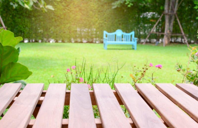 在被弄脏的树的空的透视褐色木头和椅子在庭院里有日落光背景 免版税库存照片