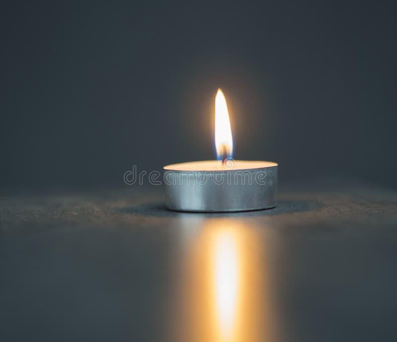在被弄脏的灰色背景的茶光蜡烛 库存图片