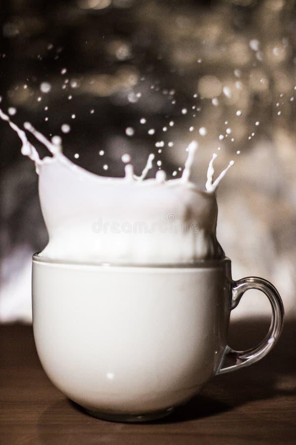 在被弄脏的背景的倾吐的牛奶 免版税库存图片