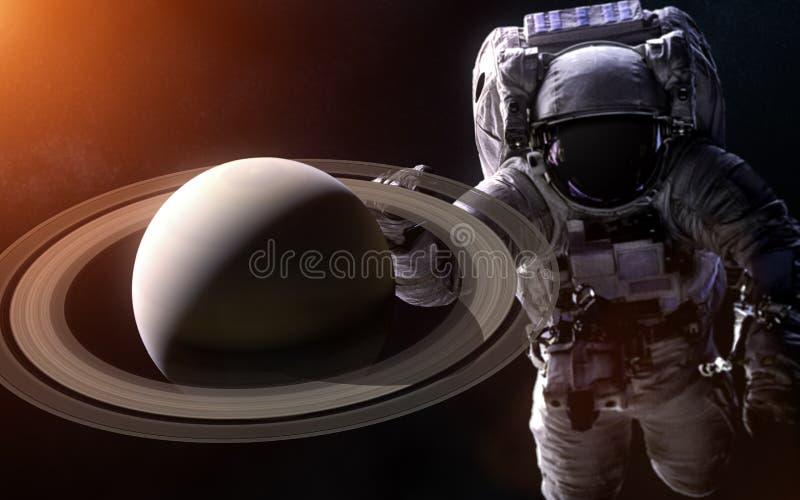在被弄脏的背景的土星与一位巨型宇航员 图象的元素由美国航空航天局装备 库存照片