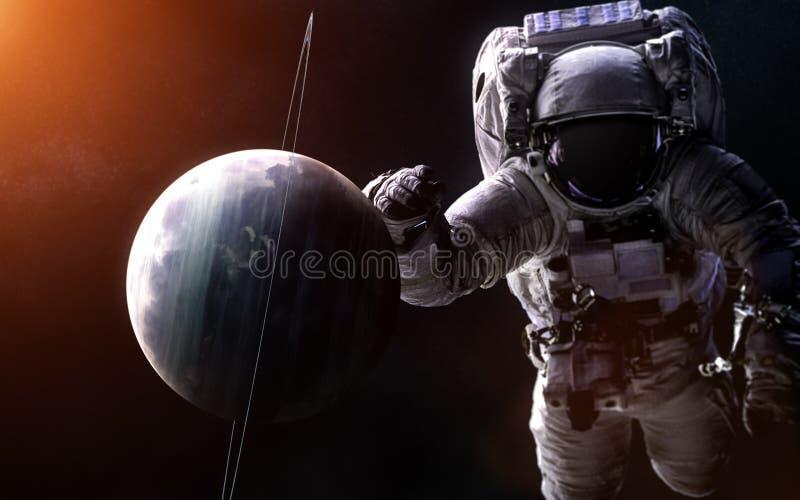 在被弄脏的背景的天王星与一位巨型宇航员 图象的元素由美国航空航天局装备 免版税库存照片