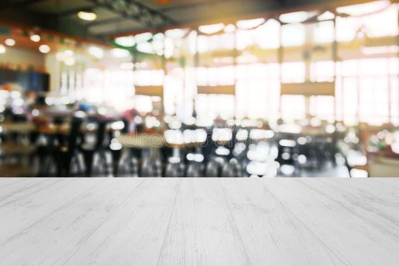在被弄脏的餐馆前面的木桌点燃背景 免版税库存照片