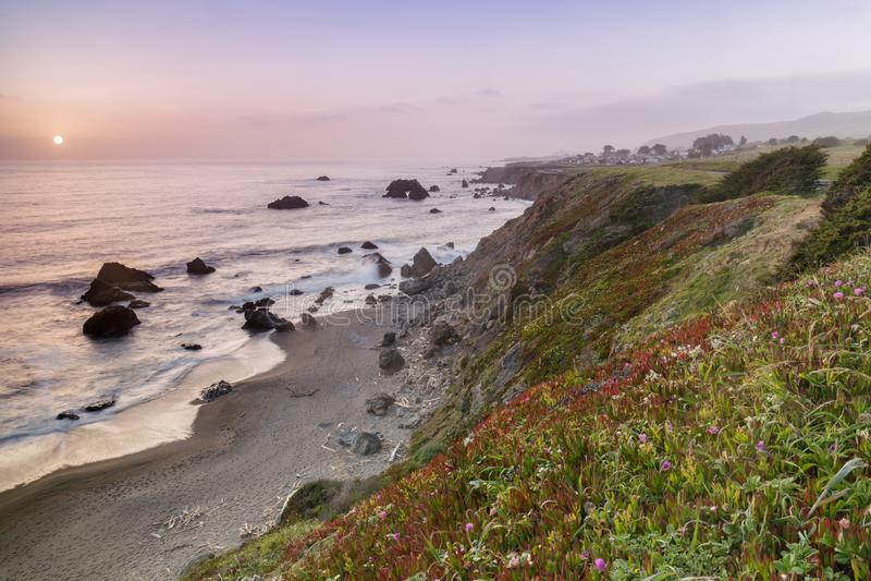 在被成拱形的岩石海滩的日落在杂货店海湾附近 免版税图库摄影