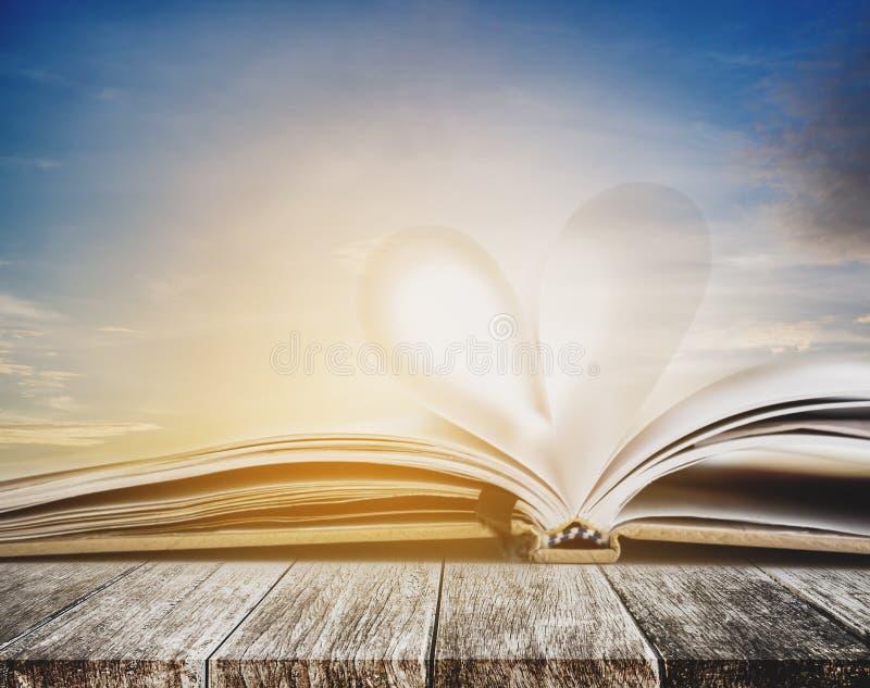 在被打开的笔记本页的心脏形状,在木桌上,与日落天空在夏天背景中,被定调子的葡萄酒颜色 库存照片
