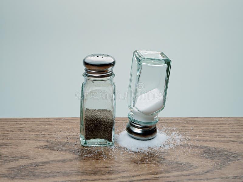 在被打翻的结束胡椒振动器旁边的溢出的盐平衡的颠倒的盐瓶 图库摄影