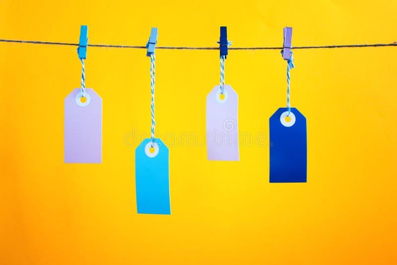 在被拍摄的黄色背景标签 四个五颜六色的空的标签在绳索垂悬别住与晒衣夹 照亮 库存图片