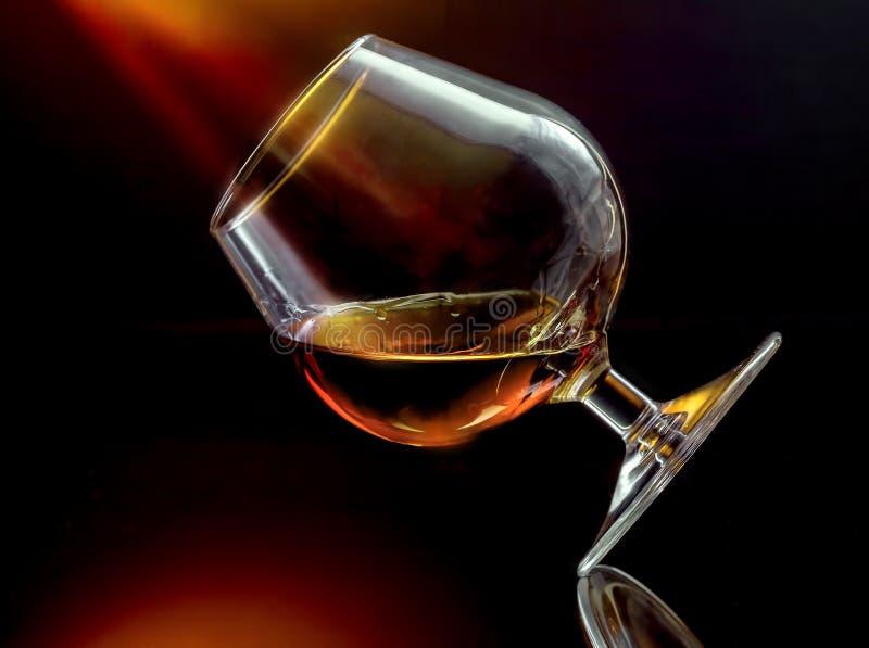 在被掀动的葡萄酒杯的科涅克白兰地 库存照片