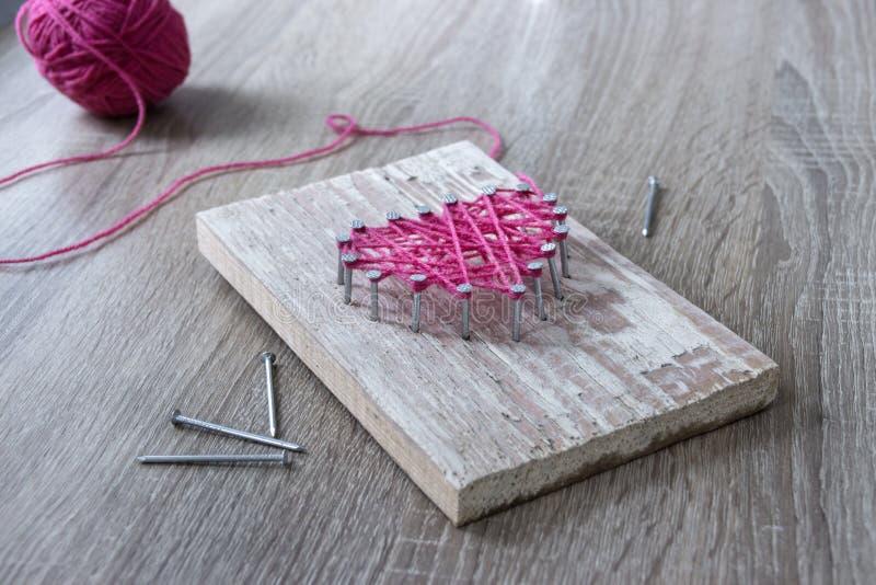 在被摆锤子钉子的一张木桌子上穿线桃红色和礼物用他们自己的手螺纹和钉子的心脏 免版税图库摄影