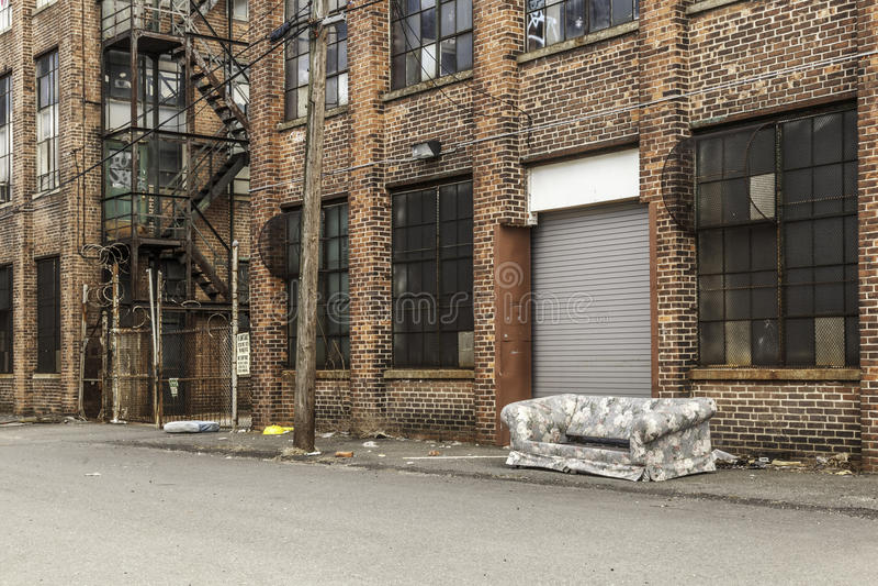 在被放弃的大厦前面的老沙发 库存照片