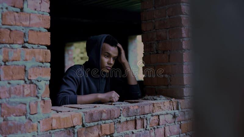 在被放弃的房子废墟中的哀伤的少年,记住家庭和童年 免版税库存图片