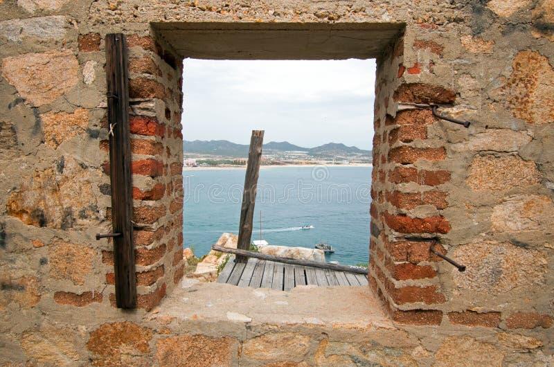 在被放弃的砖和石头大厦的窗口在Cabo圣卢卡斯小游艇船坞和港口上的小山在下加利福尼亚州墨西哥 库存图片