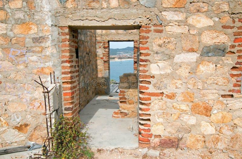 在被放弃的砖和石头大厦的门在Cabo圣卢卡斯小游艇船坞和港口上的小山在下加利福尼亚州墨西哥 免版税图库摄影