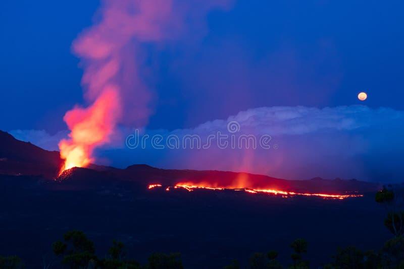 在被月光照亮蓝色nightsky的Errupting火山 库存照片