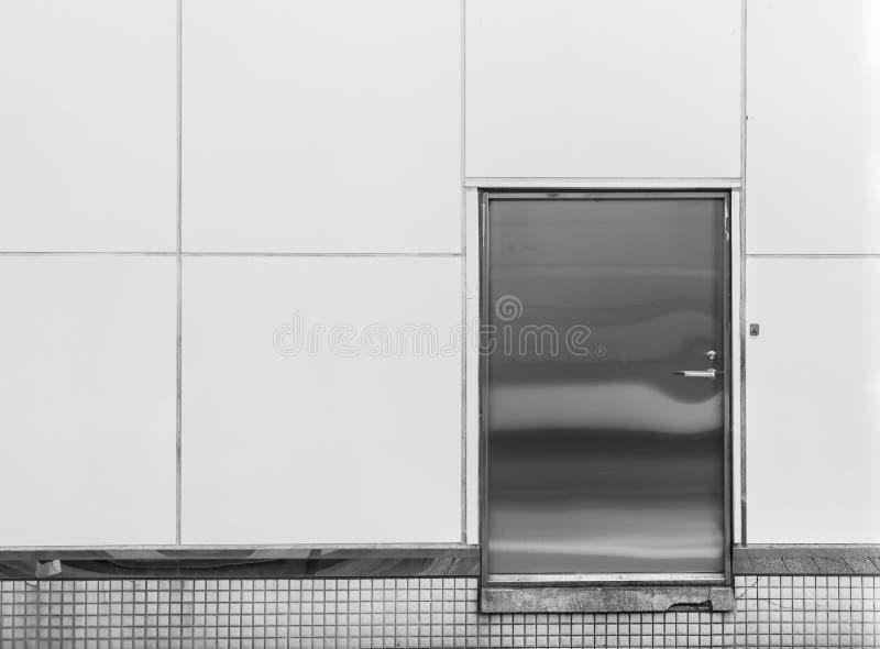 在被构造白色的墙壁的老钢金属门背景的和 免版税库存照片