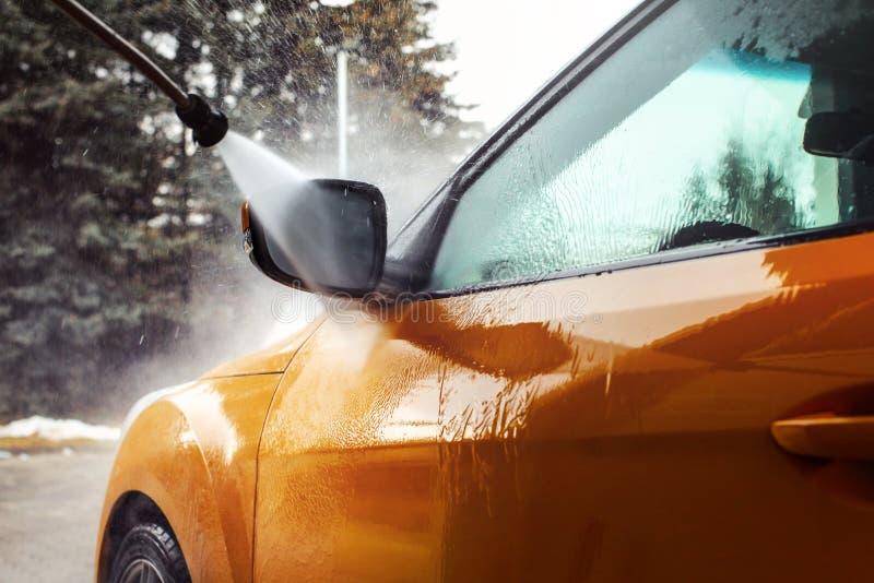 在被洗涤与喷气机wat的黑暗的黄色汽车前面镜子的细节 库存照片