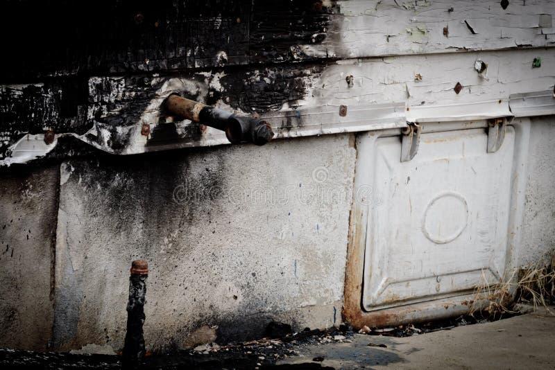 在被烧的房子的边的煤气管 免版税库存图片
