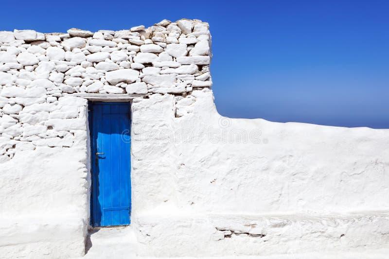 在被粉刷的墙壁的米科诺斯岛蓝色门 库存照片