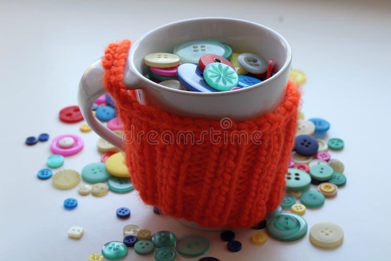 在被编织的和温暖的橙色盒包裹的一个白色杯子的多彩多姿的按钮 库存照片