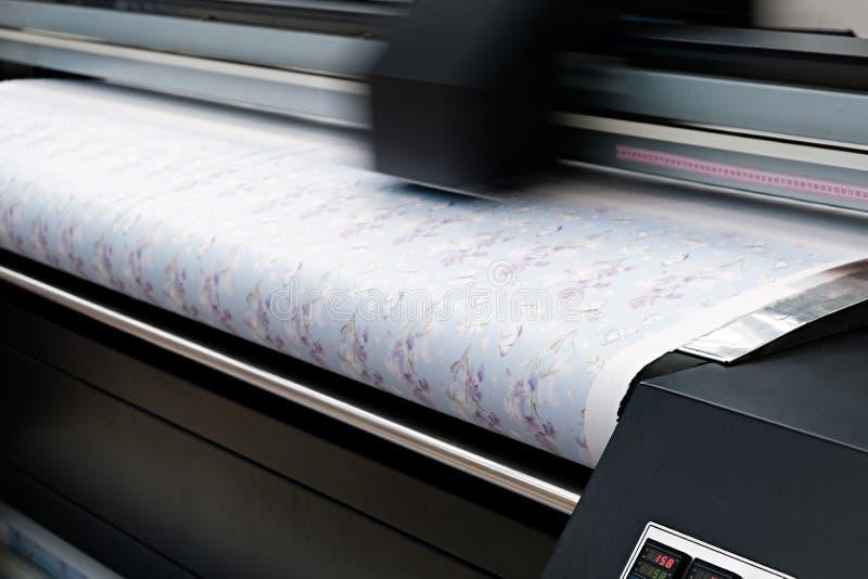 在被编织的材料的工业打印;现代数字喷墨打印机在布料帆布上把一张蓝色样式图片放 图库摄影