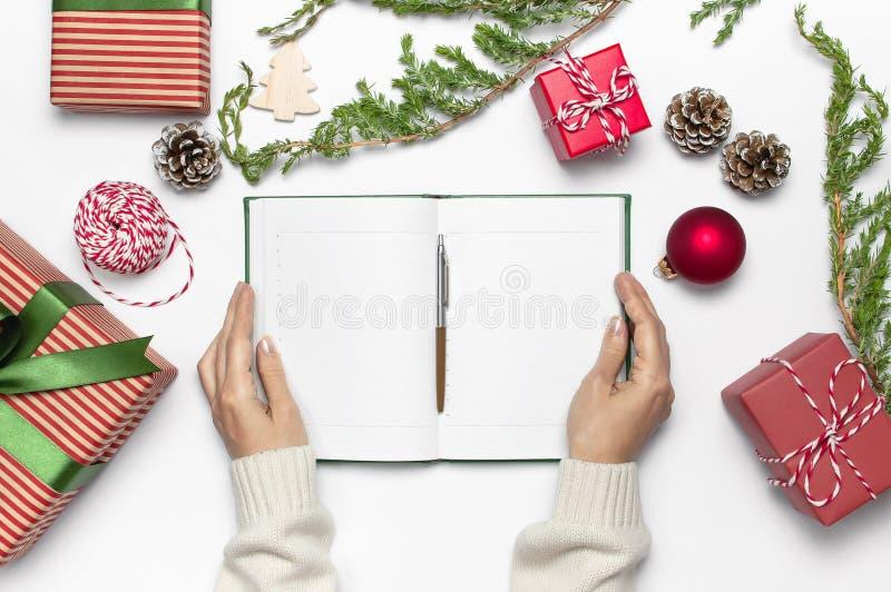 在被编织的毛线衣的女性手书写与笔在干净的笔记本计划新年,礼物盒,在白色t的冷杉分支 库存照片